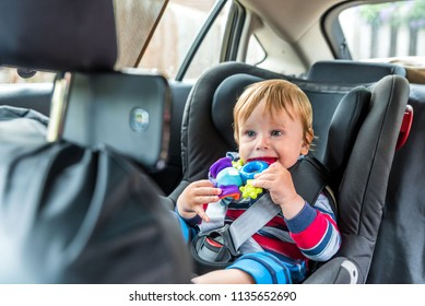 Cute blond toddler baby boy with curious happy face emotions sitting in car seat and watching a video smartphone. Internet addiction concept