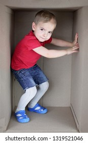 Cute blond toddler boy in red t-shirt inside cardboard box, emotional child portrait, closeup indoor, place for your text, concept