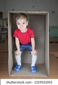 Cute blond toddler boy in red t-shirt inside cardboard box, emotional child portrait, closeup indoor, place for your text