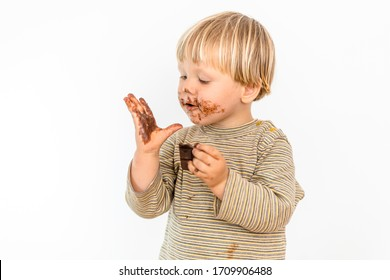 Cute blond toddler eating chocolate bar with great pleasure, isolated on white background