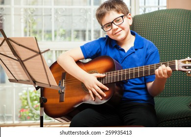 Cute blond tween with glasses playing the guitar at home and smiling