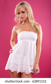 Cute blond in white dress on pink background