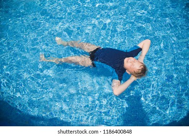 Cute blond white kid relaxing in clear blue water of outdoors sunny swimming pool laying calmly on back. Horizontal color photography.