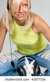 Cute blond and white rabbit listening to music