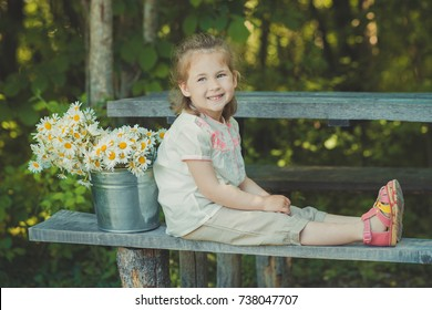 Cute blond young girl child stylish dressed in white shirt and short pants sitting on wooden bench posing bucket full of daisy chamomile mayweed.Adoreable scene.