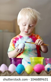 A cute, blonde, 2 year old toddler boy is concentrating as he paints on an Easter Egg in his home kitchen.