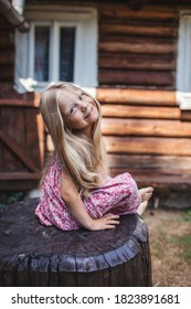Cute blonde 4-5 years old girl with long hair sitting on wood stub on the backyard of old village house, vacation in countryside, happy summertime, natural treatment and healthy beauty