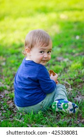 Cute blonde baby eating biscuit on the grass in outdoors spring garden
