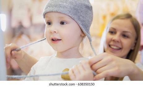 Cute blonde baby girl with mother doing shopping - buying hat