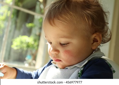 cute blonde baby sitting on a high chair