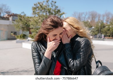 A cute blonde with a black backpack whispers in the ear of a cute brunette in a red dress and they are laughing in the street