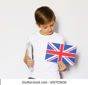Cute blonde boy in casual clothes posing with british flag