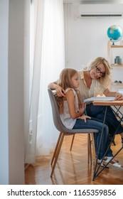 Cute blonde Caucasian schoolgirl doing homework with her mother helping. - Shutterstock ID 1165359856