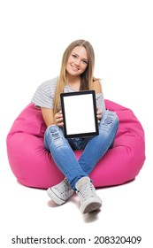 Cute blonde Caucasian teenage student girl showing tablet with white screen looking at camera smiling sitting on beanbag isolated on white background.