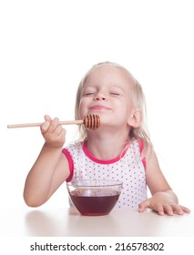 Cute blonde child eats honey from drizzle on white background