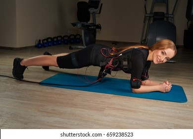 Cute blonde girl in Electrical Muscular Stimulation suits doing plank exercise on sports mat. Glowing effect. Gothic style. EMS. Workout.