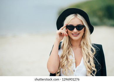 Cute blonde girl in glasses walks along the coast and enjoy life