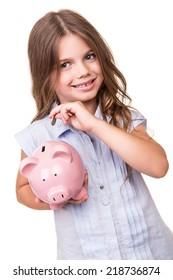 Cute blonde girl holding pink piggy bank