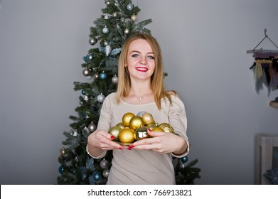 Cute blonde girl on beige dress against new year tree with with golden new year balls at studio. Happy holidays.
