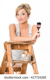 Cute blonde girl, in overalls, holding paint brush and resting on old ladder, isolated on white