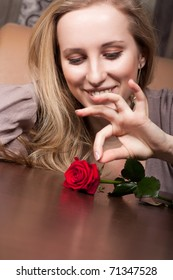 Cute blonde girl with a red rose