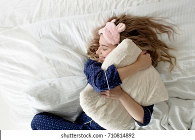 Cute blonde in her bed in blue pajamas and sleep mask, hugging pillow