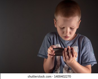 Cute blonde kid boy from school for children with poor eyesight look at smartphone screen. Shallow focus