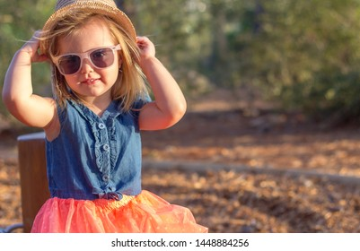 A cute blonde little girl in the park. She is wearing a hat and sunglasses