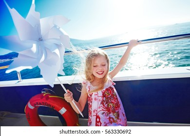 Cute blonde long haired six years old girl is playing with pinwheel on cruise ship deck, windy weather