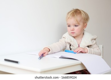 Cute blonde toddler girl drawing with colorful crayons sitting on white chair at white table indoors at home or in kindergarten