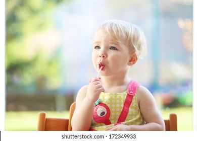 Cute blonde toddler girl eating lollipop sitting in the kitchen on a sunny summer day next to a big window with garden view