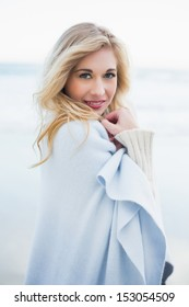 Cute blonde woman covering herself in a blanket on the beach