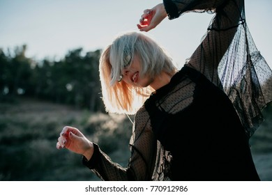 Cute blonde woman posing in profile with sunglasses and black clothes, raising arms up, with sun backlighting in nature.