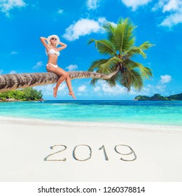 Cute blonde woman in white bikini and hat at palm tree against tropical ocean beach with inscription 2019 on white sand. Opening New year traveing season concept.