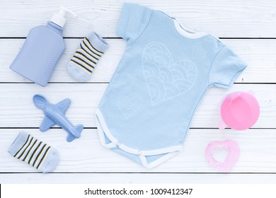 Cute blue baby clothes for boy. Bodysuit, booties, toy on white wooden background top view