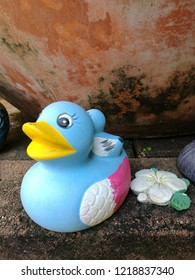 Cute blue decorative duck in garden with background of brown old clay bowl.