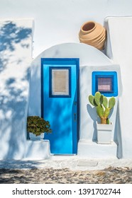 Cute blue door and window on white building. Typical house at Oia, Satorini, Greece.