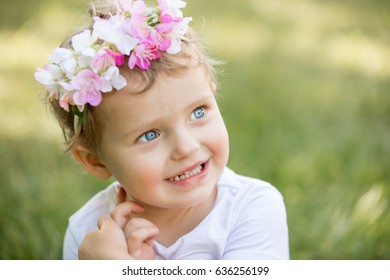 Cute blue eyes toddler girl sitting on green grass and smiling. Nice look, wreath on head.