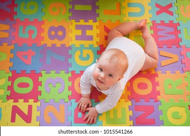 Cute blue-eyed baby smiling up while playing on tummy on alphabet mats.
