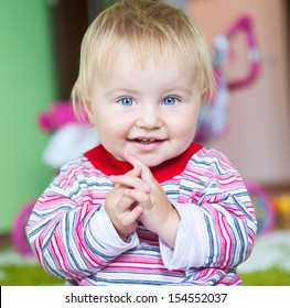 cute blue-eyed toddler in the nursery close-up claps