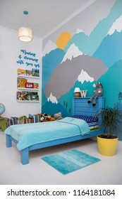 Cute boy bedroom design with a turquoise grey mountain wall mural and lots of books.