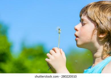 Cute Boy blowing dandelion seeds in the park