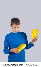 Cute boy in blue shirt looking on yellow empty lunch box with wonder. Vertical photo with grey background