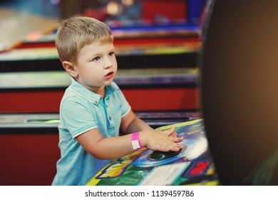 Cute boy in blue t-shirt plays arcade in game machine at an amusement park.
