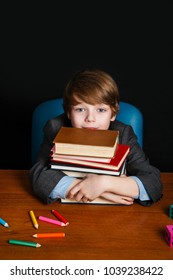 cute boy with books and sitting at a school desk . Back to school.