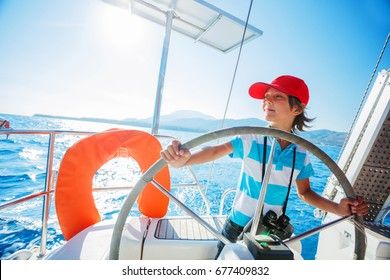 Cute boy captain on board of sailing yacht on summer cruise. Travel adventure, yachting with child on family vacation. Kid clothing in sailor style, nautical fashion.