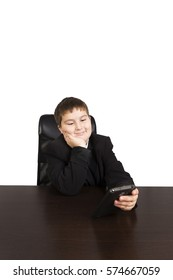 Cute  boy with a cell phone sitting at the table. Business concept