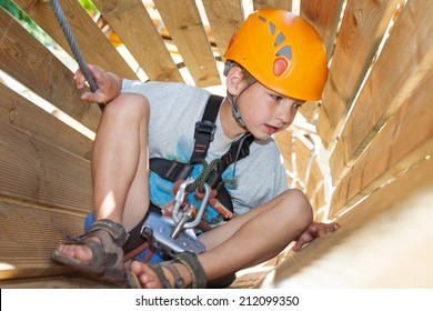 Cute boy with climbing equipment in an adventure park in a wooden tunnel