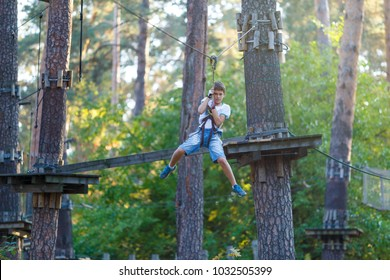 cute boy  climbs on a very risky treetops in rope adventure park in the summer
