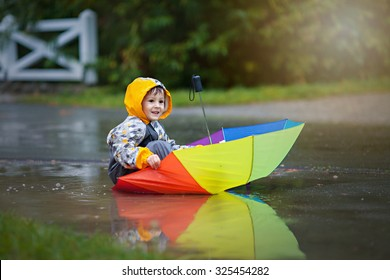 Cute boy with colorful rainbow umbrella on a rainy day, having fun playing in the park in muddy puddles